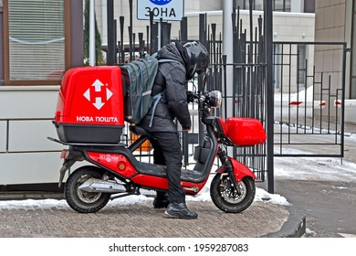 KIEV, UKRAINE - FEB 02, 2021: unknown young Nova Poshta courier in black suit on motorcycle delivers items in large red container on February 02, 2021 in Kiev, Ukraine.