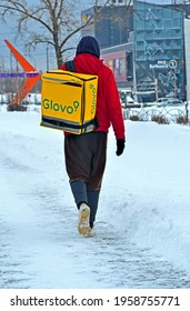 KIEV, UKRAINE - FEB 10, 2021: unknown young walking Glovo courier in red suit delivers food in large yellow container from supermarket on February 10, 2021 in Kiev, Ukraine.