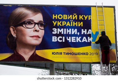 KIEV, UKRAINE - Feb 13, 2019: Presidential election campaignin Ukraine. A man glues a billboard election poster of Yulia Tymoshenko