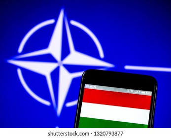 KIEV, UKRAINE - Feb 23, 2019: Hungary flag on the phone display on the background of the NATO flag