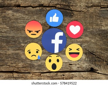 Kiev, Ukraine - February 07, 2017: Facebook like button 6 Empathetic Emoji Reactions printed on white paper and placed on wooden background. Facebook is a well-known social networking service