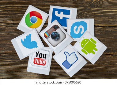 Kiev, Ukraine - February 09, 2015: Set of most popular social media icons: Twitter,Youtube, Instagram, Facebook, Skype, Google Chrome, Android,  printed on paper and scattered on the wooden table