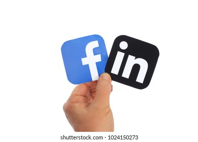 Kiev, Ukraine -  FEBRUARY 13, 2018: Hand holds Facebook and  LinkedIn icons printed on paper on blue paper background. Facebook is a well-known social networking service