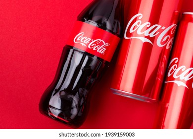 Kiev, Ukraine - February 14, 2021: One bottle and two cans of Coca-Cola lie on a red background