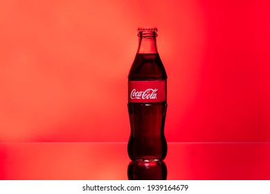Kiev, Ukraine - February 14, 2021: Glass bottle of 0.25 liters of the world famous American Coca-Cola drink stands on a red-orange background