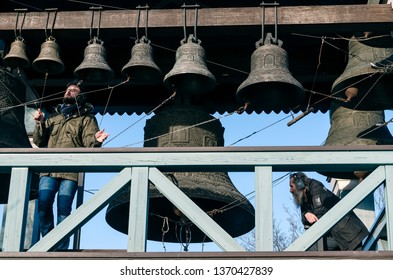 Kiev / Ukraine - February 16, 2019: Two ringers men on belfry perfoming chime near Holy Trinity and St. Jonah's Monastery