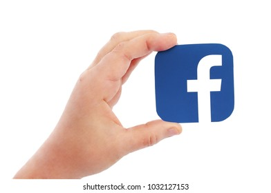 Kiev, Ukraine -  FEBRUARY 17, 2018: Hand holds Facebook  icons printed on paper on blue paper background. Facebook is a well-known social networking service
