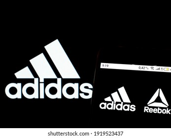 KIEV, UKRAINE - February 18, 2021: In this photo illustration Adidas and Reebok logo is seen displayed on a smartphone