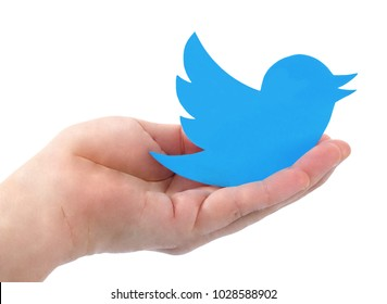 Kiev, Ukraine -  FEBRUARY 19, 2018: Hand holds Twitter  icons printed on paper on blue paper background. Facebook is a well-known social networking service