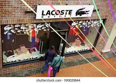 KIEV - UKRAINE - FEBRUARY 2017. Village outlet Manufacture, top view store Lacoste Outlet with young girl and boy. People are coming in shop.