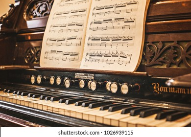KIEV, UKRAINE - February 2018: Retro ancient home organ with music book on it at one of homes in Kiev. Home organ, music book and piano keyboard close up, Kiev, Ukraine.