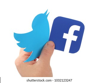 Kiev, Ukraine -  FEBRUARY 24, 2018: Hand holds Facebook and  Twitter icons printed on paper on blue paper background. Facebook is a well-known social networking service