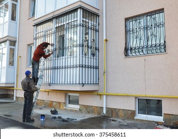 KIEV, UKRAINE - FEBRUARY, 5, 2016: Contractors install window iron security bars