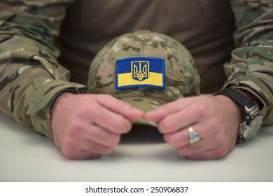KIEV, UKRAINE - FEBRUARY, 8, 2015: A man in military uniform holds a camouflage hat with a stripe in the form of a flag of Ukraine
