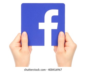 Kiev, Ukraine - January 15, 2016: Hands hold facebook logo printed on paper on white background. Facebook is a well-known social networking service.