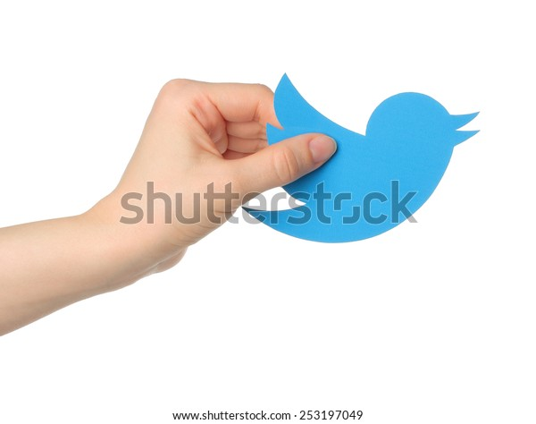 KIEV, UKRAINE - JANUARY 16, 2015: Hand holds twitter logotype bird printed on paper. Twitter is an online social networking service that enables users to send and read short messages.