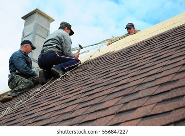 KIEV - UKRAINE, JANUARY - 16, 2017: Roofing Construction. Roofing Contractors Install New House  with Asphalt Shingles Roofing Construction. Roofers with safety rope. Roofing Contractor.