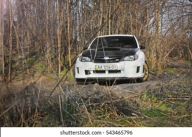 Kiev, Ukraine; January 20, 2014. Subaru Impreza WRX STI in the forest. in the foreground branches. impassability of roads. Fast and the Furious. Japanese supercar. Editorial photo.