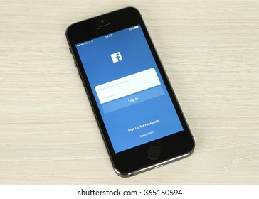 Kiev, Ukraine - January 20, 2016:iPhone with Facebook login page on its screen on wooden background