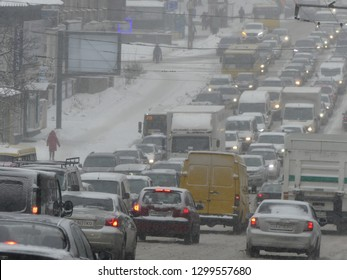 Kiev, Ukraine - January 2019: Stream of cars on the snow track. Traffic jam on the snowy road. Car moving on a snowy road in the city.