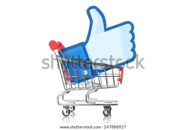 KIEV, UKRAINE - JANUARY 24, 2015: Facebook thumbs up sign printed on paper and placed into shopping cart on white background. Facebook is a well-known social networking service.