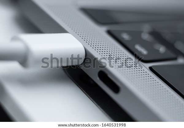 Kiev, Ukraine - January 24, 2020: White charging cable plugged into usb type-c connector on macbook pro 2019