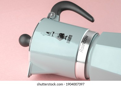 Kiev, Ukraine - January 26, 2021: BIALETTI metal coffee maker in green color isolated, geyser coffee maker on pink background
