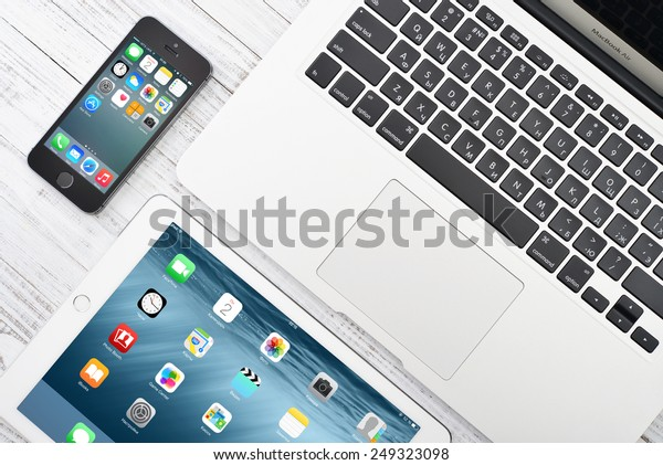 KIEV, UKRAINE - JANUARY 29, 2015: Apple iPhone 5s, iPad Air 2 and MacBook Air on table. Apple Inc. is an American multinational corporation that designs, develops, and sells consumer electronics.