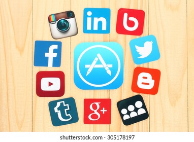 KIEV, UKRAINE - JULY 01, 2015: Around AppStore icon are placed famous social media icons such as: Facebook, Twitter, Blogger, Linkedin and others, printed on paper and placed on wooden background.