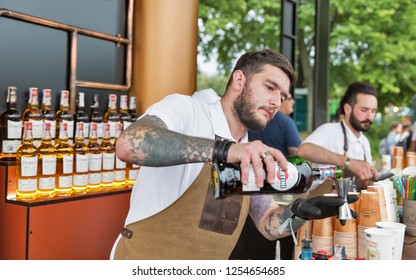 KIEV, UKRAINE - JULY 04, 2018: Young man bartender works in Bacardi outdoor bar at the Atlas Weekend Festival in National Expocenter. Bacardi is the largest family owned spirits company in the world.