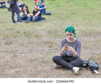 KIEV, UKRAINE - JULY 04, 2018: Young girl music fan with green hairs uses smartphone during visit to outdoor music concert at the Atlas Weekend music festival in National Expocenter.