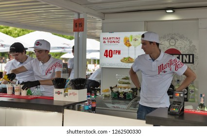 KIEV, UKRAINE - JULY 07, 2018: Young men bartenders work in Martini outdoor bar at the Atlas Weekend Festival in National Expocenter. Bacardi is the largest family owned spirits company in the world.