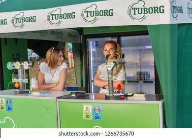 KIEV, UKRAINE - JULY 08, 2018: Young woman bartenders work in Tuborg beer outdoor bar at the Atlas Weekend Festival in National Expocenter. Tuborg is a Danish brewing company, part of Carlsberg Group.