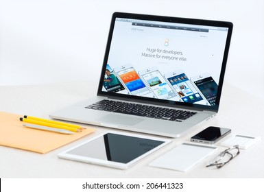 KIEV, UKRAINE - JULY 10, 2014: Studio shot of brand new Apple MacBook Pro presenting new iOS 8 for developers, with Apple mobile devices and office tools on a modern desk.