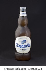 KIEV, UKRAINE - JULY 14, 2012: Hoegaarden wheat Belgian beer cold bottle against black. Hoegaarden beer is unfiltered and therefore cloudy in appearance, it is spiced with coriander and orange peel.