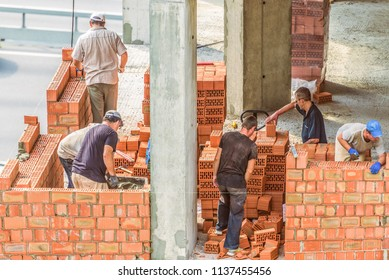 Kiev, Ukraine - July 17, 2018:  Workers work at the construction site. Work is under way to lay a wall of red brick.