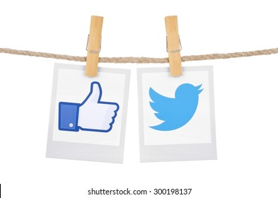 KIEV, UKRAINE - JULY 26, 2015: Popular social media Facebook, Twitter hanging on the clothesline isolated on white background.