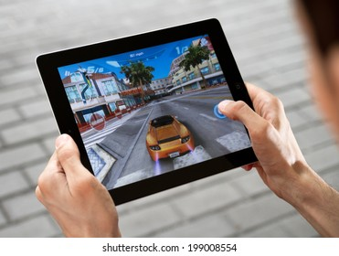 KIEV, UKRAINE - JULY 31, 2011:  Man playing Asphalt 6 game on brand new Apple iPad. Apple iPad2 develop by Apple inc. and launched in March, 2011. Asphalt 6 is a game application, develop by Gameloft.