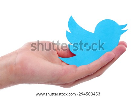 KIEV, UKRAINE - JULY 8, 2015: Hand holds twitter logotype bird printed on paper. Twitter is an online social networking service.