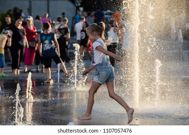 KIEV, UKRAINE - Jun 05, 2018: Cheerful and happy girl playing in a water fountain and enjoying the cool streams of water in a hot day. Hot summer.