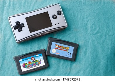 Kiev, Ukraine - June 04, 2020: Game Boy Micro 2005 with cartridges, special edition. popular handheld video game device, retro games installation. place for inscription. on blue background