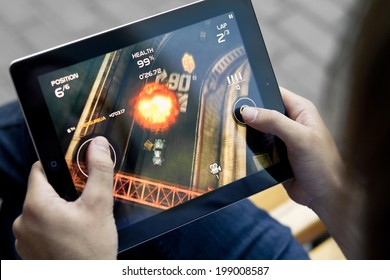 KIEV, UKRAINE - JUNE 05, 2011: Man playing in Death Rally game on brand new Apple iPad. Apple iPad2  was released in March, 2011. Death Rally is popular game, develop by Remedy Entertainment.