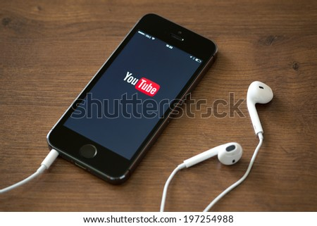 KIEV, UKRAINE - JUNE 05, 2014: Brand new Apple iPhone 5S with YouTube app on the screen lying on desk with headphones. YouTube is the popular online video-sharing website, founded in February 14, 2005