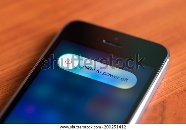 KIEV, UKRAINE - JUNE 12, 2014: Brand new Apple iPhone 5S with slide to power off option on a screen lying on a desk. Apple iPhone 5s, is developed by Apple inc. and was released on September 20, 2013.