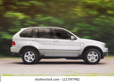 Kiev, Ukraine - June 16, 2018: Silver off-road BMW X5 in motion against the background of the forest