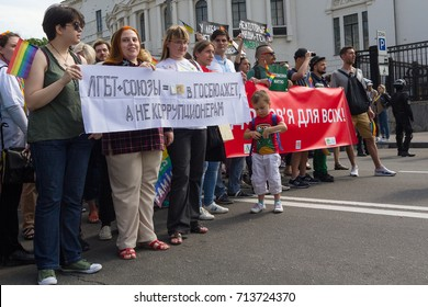 "Kiev, Ukraine - June 18, 2017: Participants in the gay parade with banners with the inscriptions ""LGBT plus unions - getting into the budget, not corrupt"" Health for All in Ukrainian"