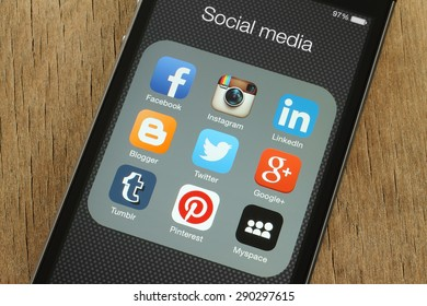 KIEV, UKRAINE - JUNE 23, 2015: iPhone with popular social media icons on its screen on wooden background