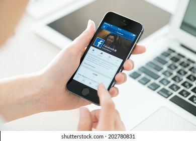 KIEV, UKRAINE - JUNE 27, 2014: Person holding a brand new Apple iPhone 5S with Facebook profile on the screen. Facebook is a social media online service for microblogging and networking communication.