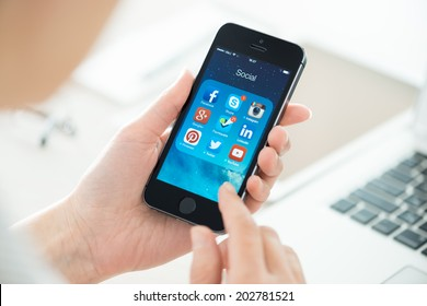 KIEV, UKRAINE - JUNE 27, 2014: Woman looking on social media applications on a brand new black Apple iPhone 5S, which is designed and developed by Apple inc. and was released on September 20, 2013.