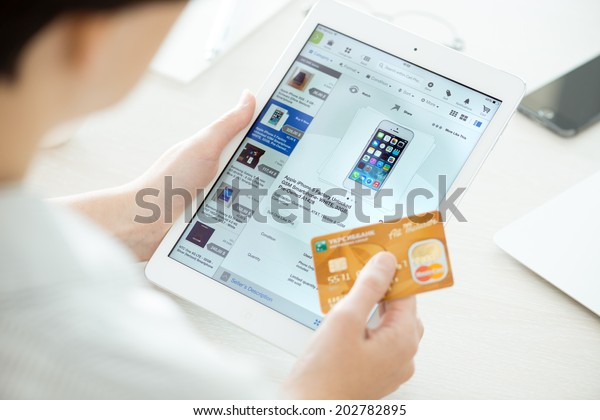 KIEV, UKRAINE - JUNE 27, 2014: Person holding a credit card and trying to buy a new Apple iPhone 5 with eBay application on a brand new Apple iPad Air. eBay is the online auction and shopping website.